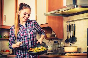 Junge Frau schwenkt Pfanne beim Kochen