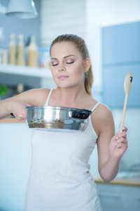 Eine junge Dame geniesst den Geruch des gekochten Gerichts
