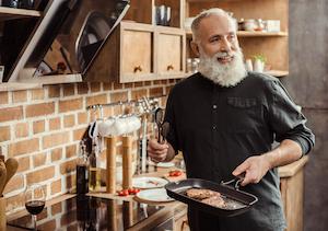 Ein Mann kocht Steak in einer Grillpfanne